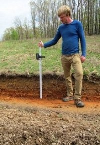 Adam Haugeberg, the farms full-time permaculture designer and worker, measures the depth of the deepest swales. The swales varied in depth of between 14-20 inches. Where the soil was softer, the blade dug in deeper. With this kind of blade there is not a way to pre-set the depth so the operator's skill and ability is important.