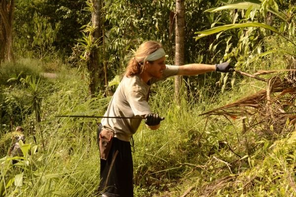The author using a machete to clear a site for planting.