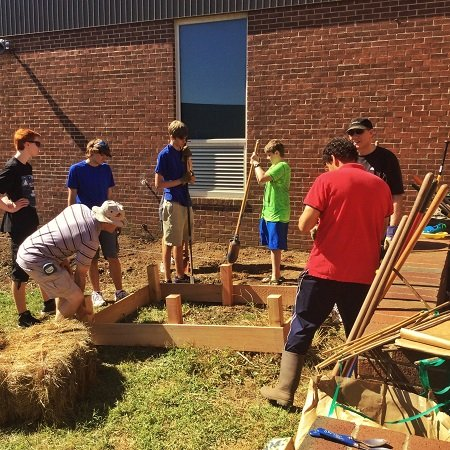 A troop of boy scouts and their dads create garden beds for the students