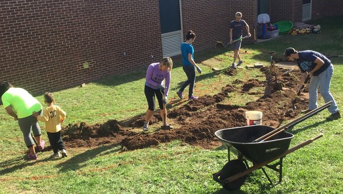 Permablitz DC, parents and students digging swales at the Rolling Ridge