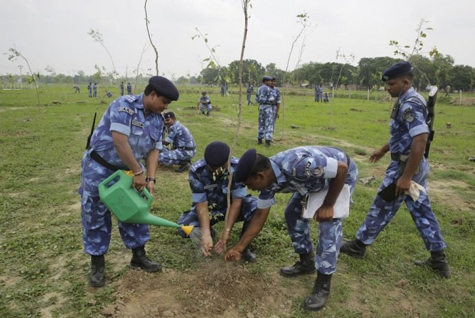 Para-military force soldiers plant saplings. Image credit: AP Photo/Rajesh Kumar Singh