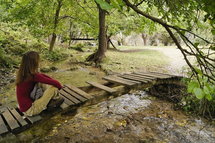 Beautiful young girl relaxing on a wooden bridge in the forest