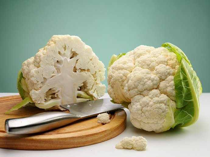 ripe cauliflower on the table over green background